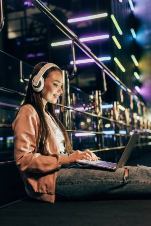 Photo for Smiling woman in pink jacket with headphones using laptop in night city - Royalty Free Image