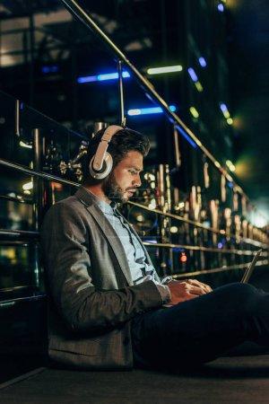 Photo pour Homme d'affaires beau dans l'usure formelle avec des écouteurs se reposant et utilisant l'ordinateur portatif dans la ville de nuit - image libre de droit