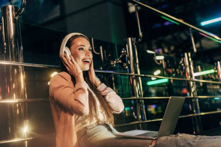 Photo for Smiling woman in pink jacket listening music with headphones in night city - Royalty Free Image