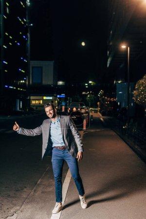 Photo pour Homme d'affaires beau dans le sourire formel d'usure et le pouce dans la ville de nuit - image libre de droit