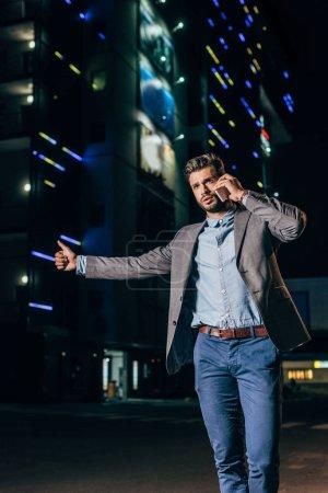 Photo pour Bel homme d'affaires dans l'usure formelle parlant sur le smartphone et le pouce dans la ville de nuit - image libre de droit