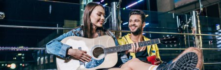 Photo for Panoramic shot of handsome boyfriend with plastic cup and attractive girlfriend playing acoustic guitar in night city - Royalty Free Image