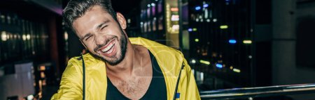 Photo for Panoramic shot of handsome man in yellow jacket smiling in night city - Royalty Free Image