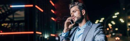 Photo pour Tir panoramique de l'homme d'affaires beau dans l'usure formelle parlant sur le smartphone dans la ville de nuit - image libre de droit