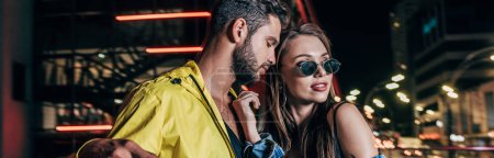 Photo for Panoramic shot of handsome boyfriend and attractive girlfriend hugging in night city - Royalty Free Image