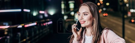 Photo for Panoramic shot of attractive woman in pink jacket smiling and talking on smartphone in night city - Royalty Free Image