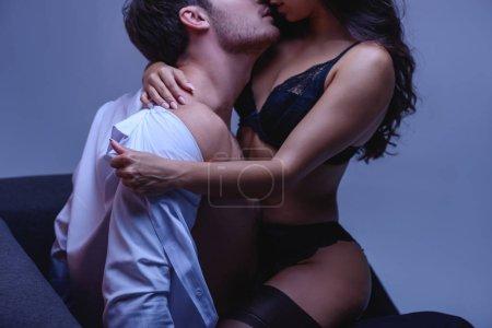 Photo pour Vue recadrée de fille passionnée en lingerie noire décoller chemise de petit ami sur fond violet - image libre de droit
