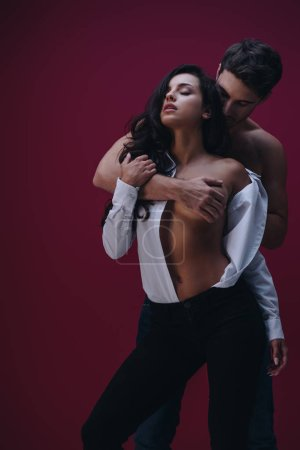 young man embracing sexy girl in unbuttoned white shirt on dark background
