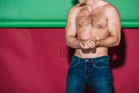 Foto de Cropped view of shirtless man in denim jeans posing on green and red background - Imagen libre de derechos