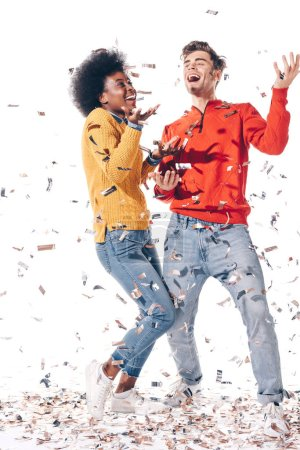 Photo pour Happy multiethnic couple dancing with confetti, isolated on white - image libre de droit