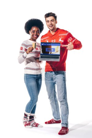 Photo pour Couple multiculturel détenteur d'une carte de crédit et d'un ordinateur portable avec billets d'avion site Web, isolé sur blanc - image libre de droit