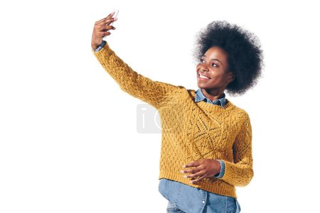 Photo for Beautiful african american girl taking selfie on smartphone, isolated on white - Royalty Free Image