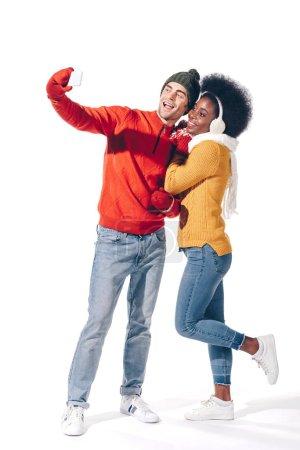 Photo pour Beau couple interracial prenant selfie sur smartphone, isolé sur blanc - image libre de droit