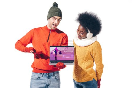 multicultural couple in winter sweaters, gloves and hat holding laptop with online shopping website, isolated on white