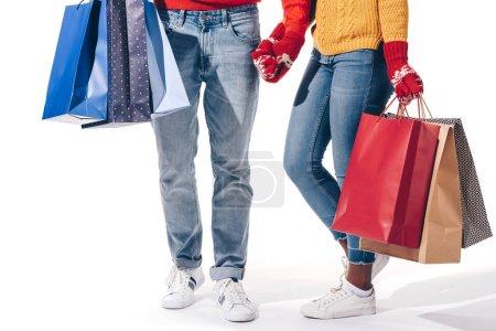 Photo pour Vue recadrée du couple avec sacs à provisions tenant la main, isolé sur blanc - image libre de droit