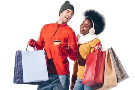 Photo pour Beau couple multiethnique en chandails d'hiver tenant carte de crédit et sacs à provisions, isolé sur blanc - image libre de droit
