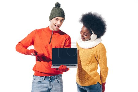 beautiful multicultural couple in winter sweaters, gloves and hat holding laptop with blank screen, isolated on white