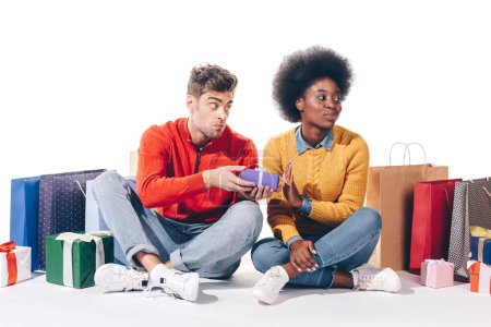 Photo pour Heureux couple multiethnique avec des sacs à provisions et des cadeaux, isolé sur blanc - image libre de droit