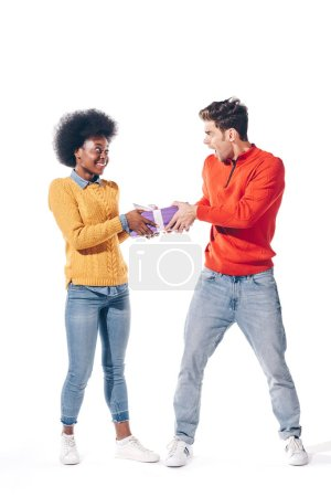 Photo for Shocked boyfriend and smiling african american girlfriend holding gift box, isolated on white - Royalty Free Image