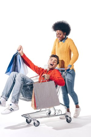 Photo for Young multicultural couple having fun in shopping cart with shopping bags, isolated on white - Royalty Free Image
