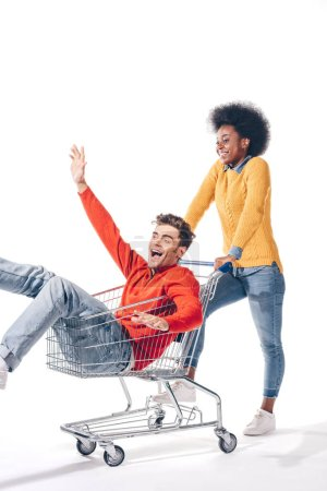 Photo for Multicultural couple having fun with shopping cart, isolated on white - Royalty Free Image
