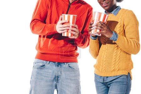 cropped view of multicultural couple holding popcorn, isolated on white