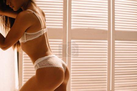 Photo pour Vue recadrée de fille passionnée posant en dentelle blanche lingerie près de l'écran pliant - image libre de droit