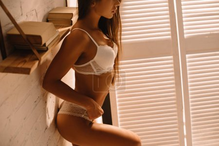 Photo pour Cropped view of seductive girl with long hair posing in white lace lingerie near folding screen - image libre de droit
