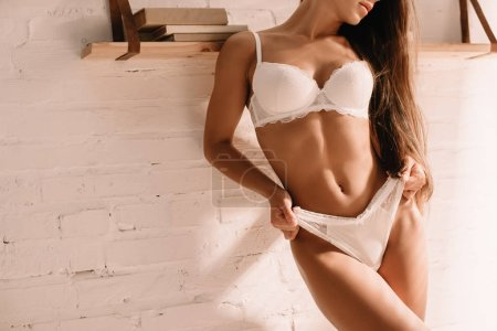 Photo pour Cropped view of beautiful sexy woman in white lingerie posing near wall - image libre de droit
