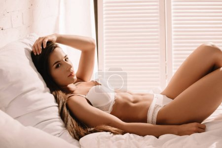 Photo pour Beautiful sexy girl with long hair in white lace lingerie posing on bed - image libre de droit