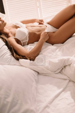 Photo pour Cropped view of passionate girl in white lingerie posing on bed - image libre de droit