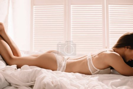 Photo pour Vue recadrée de femme sexy en dentelle blanche posant sur le lit - image libre de droit