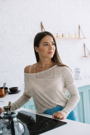 Photo pour Beautiful smiling woman with long hair posing in kitchen at home - image libre de droit