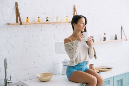 happy young woman holding cup of coffee in kitchen