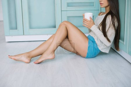 Photo for Cropped view of woman with coffee sitting on floor in kitchen - Royalty Free Image