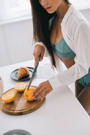 Photo pour Cropped view of sexy woman in lingerie cutting oranges for juice on kitchen - image libre de droit