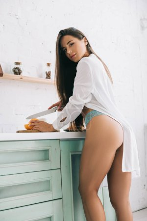 Photo pour Attractive sexy girl in lingerie cutting oranges for juice on kitchen - image libre de droit
