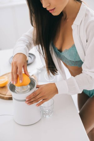 Photo pour Cropped view of sexy girl in lingerie making orange juice with citrus squeezer on kitchen - image libre de droit