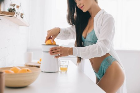 Photo pour Cropped view of happy girl in lingerie making orange juice with citrus squeezer on kitchen - image libre de droit