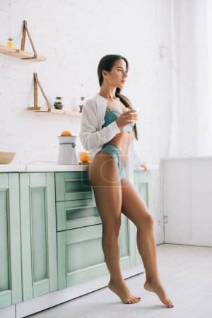 Photo pour Seductive girl in lingerie holding glass of orange juice on kitchen in the morning - image libre de droit