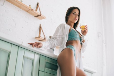 Photo pour Beautiful sexy woman in lingerie drinking orange juice on kitchen in the morning - image libre de droit