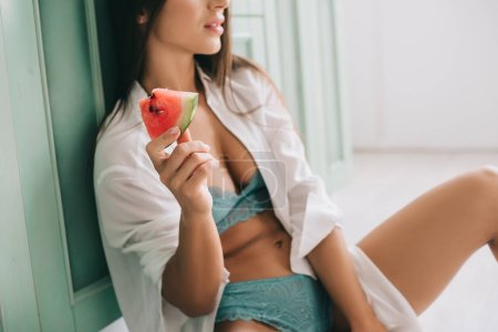 Photo for Cropped view of girl in lingerie and white shirt eating watermelon on floor in kitchen - Royalty Free Image