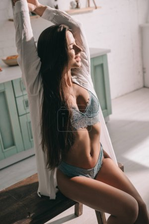 Photo pour Smiling woman with long hair posing in blue lingerie and white shirt in kitchen in the morning - image libre de droit