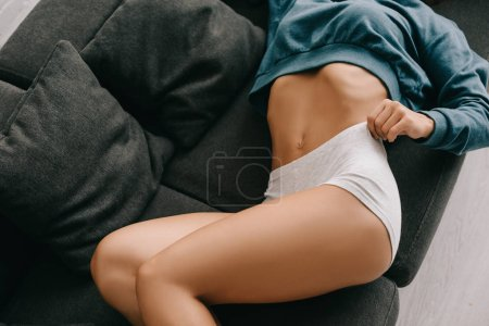 Photo pour Cropped view of sexy slim girl in white panties lying on sofa - image libre de droit