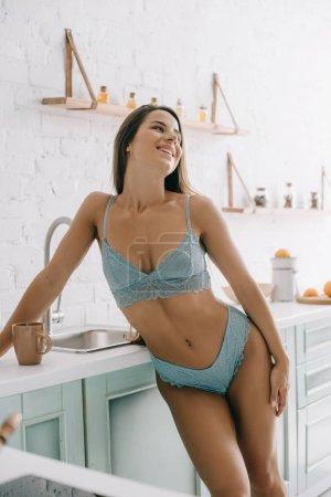 Photo pour Belle fille gaie en lingerie bleue debout dans la cuisine avec tasse de café - image libre de droit