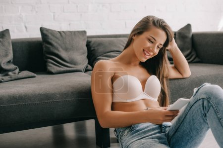 Photo pour Smiling woman in white bra and jeans using smartphone while sitting on floor near sofa - image libre de droit