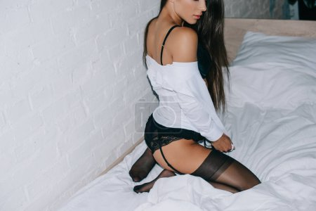 Photo pour Cropped view of beautiful sensual girl in black lingerie and stockings posing on bed - image libre de droit