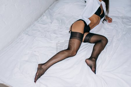 Photo for Cropped view of sexy young woman in black lingerie and stockings posing on bed - Royalty Free Image