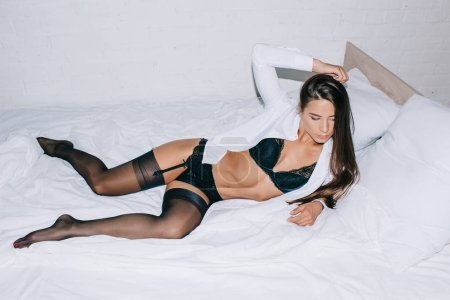 Photo for Passionate young woman in black lingerie and stockings posing on bed - Royalty Free Image