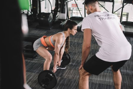 Photo for Selective focus of personal trainer looking at athletic sportswoman lifting barbell - Royalty Free Image